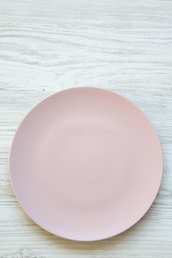 Lege roze plaat op witte houten oppervlakte De hoogste vlakke mening, van hierboven, legt stock foto