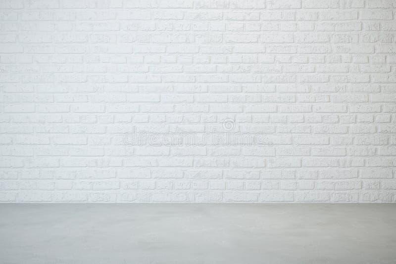 Lege ruimte met bakstenen muur en concrete vloer stock afbeeldingen