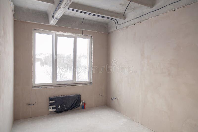 Lege ruimte met een venster en een batterij in een huis in aanbouw, gepleisterd muren, screed op de vloer, concrete op verscheide royalty-vrije stock fotografie