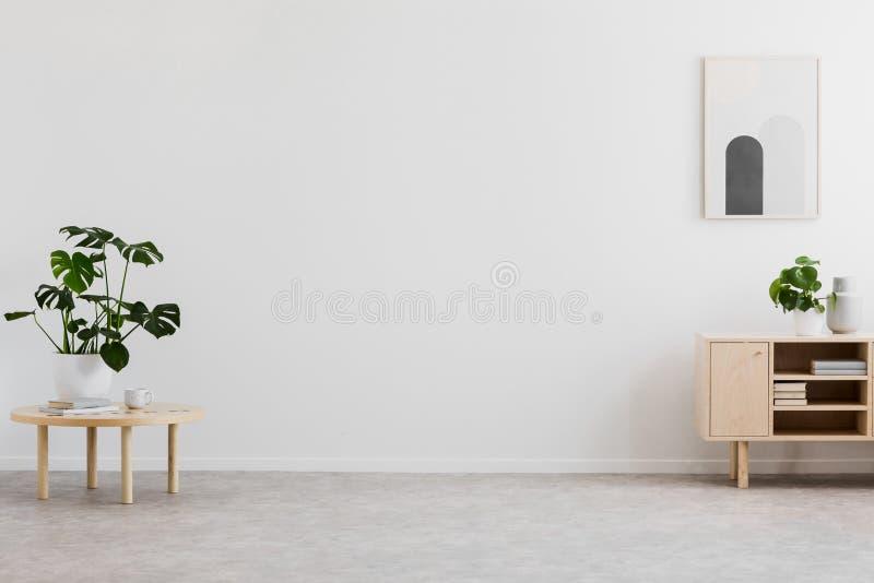 Lege ruimte voor uw bank in echte foto van helder woonkamerbinnenland met verse installaties, eenvoudige affiche en boeken op hou royalty-vrije stock afbeeldingen