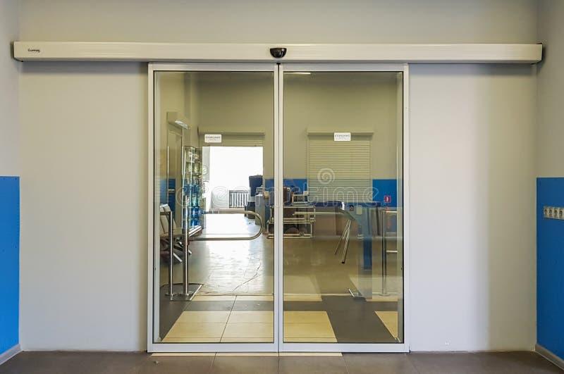 Lege schuifglas aan de voorkant van het vliegveld Glazen deuren op kantoor Glasingang Ingang op de administratie stock afbeelding