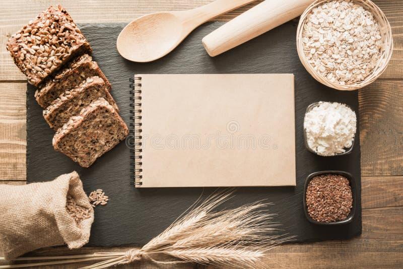 Lege spatie voor een recept van brood met ingrediënten, bloem, tarwe, brood, rogge, lijnzaad rond op zwarte leischotel Hoogste me stock afbeelding