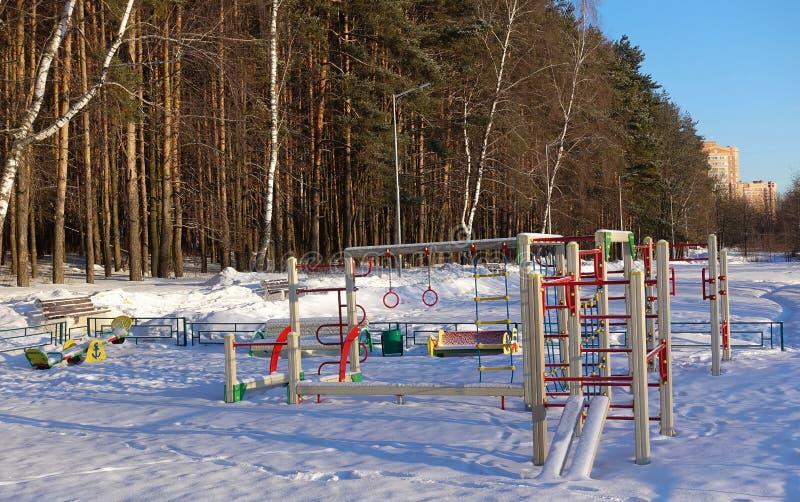 Lege speelplaats voor kinderen op een ijzige sneeuwdie de winterdag met sneeuw zonder mensen wordt behandeld Russische speelplaat stock fotografie