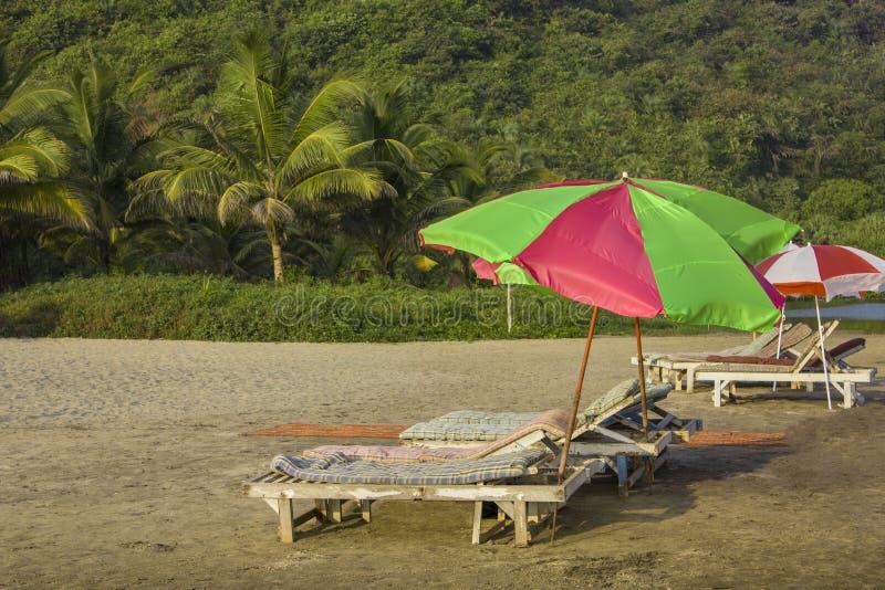 Lege strandlanterfanters met matrassen onder heldere grote zonparaplu's op het zand tegen de achtergrond van de groene palmwilder royalty-vrije stock afbeeldingen