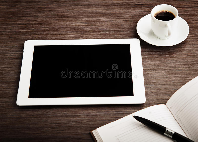 Lege tablet en een koffie op het bureau stock afbeeldingen