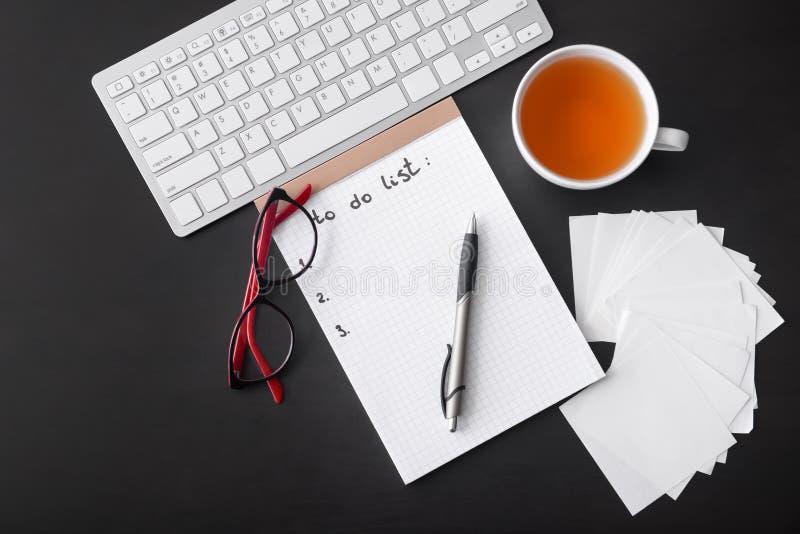 Lege takenlijst, computertoetsenbord en kop thee op donkere lijst stock foto