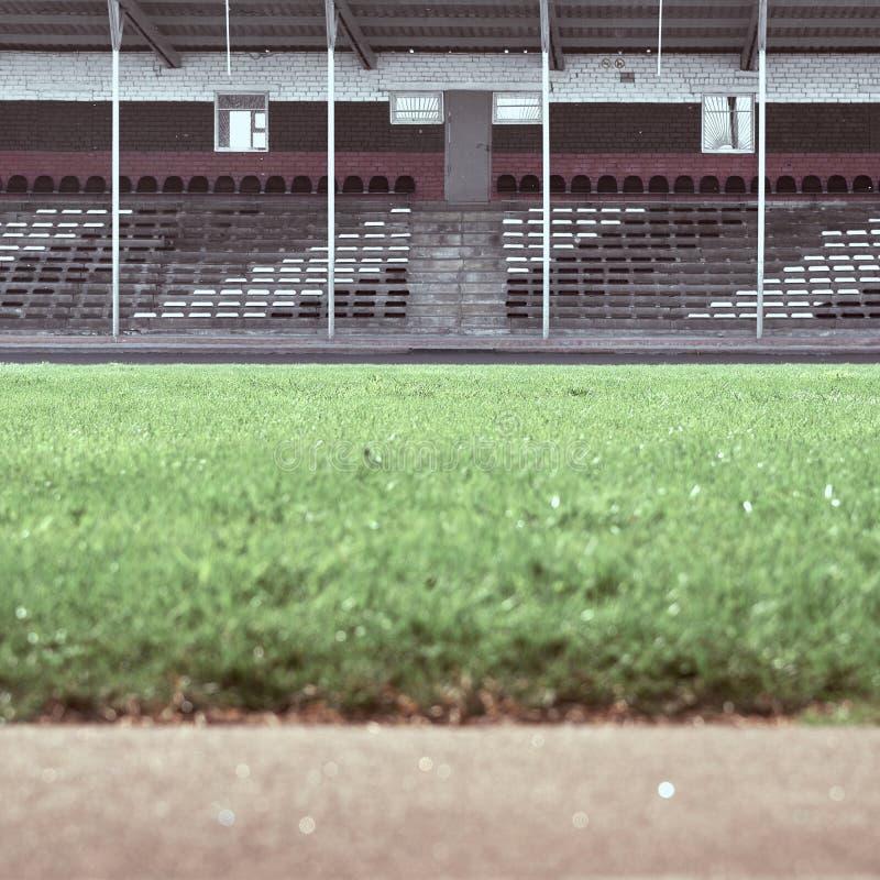 Lege tribunes bij het stadion In de voorgrond is een groen gebied in onduidelijk beeld royalty-vrije stock afbeelding