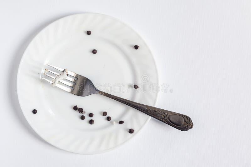 Lege vuile witte plaat en vork op de witte achtergrond Vuile plaat met stukken en crumbs dessert royalty-vrije stock foto