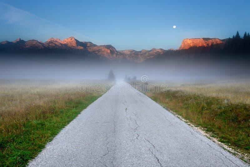 Lege weg in de bergen bij dageraad stock afbeelding