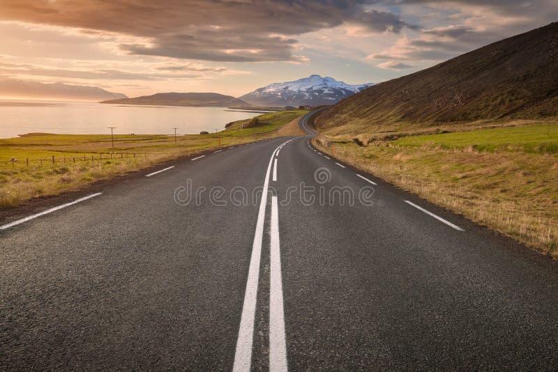 Lege weg in Noord-IJsland bij zonsondergang stock afbeeldingen