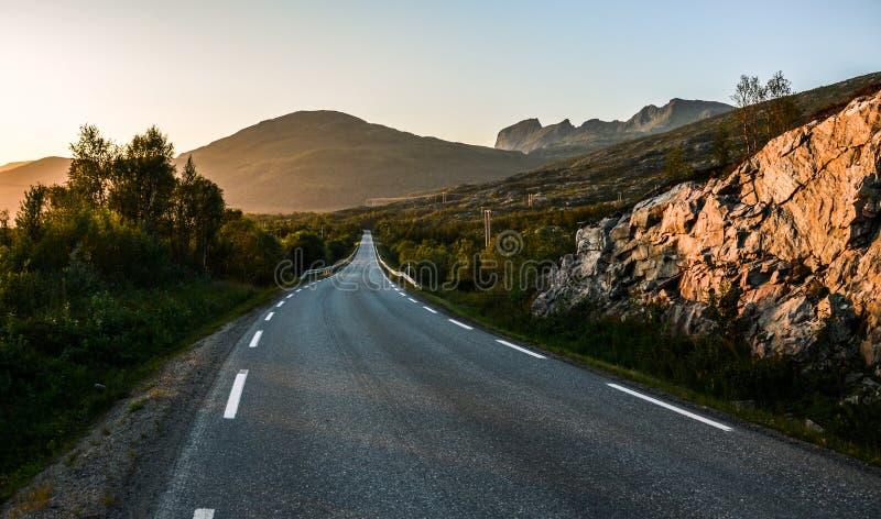 Lege weg tijdens de zonsondergang in noordelijk Noorwegen stock fotografie