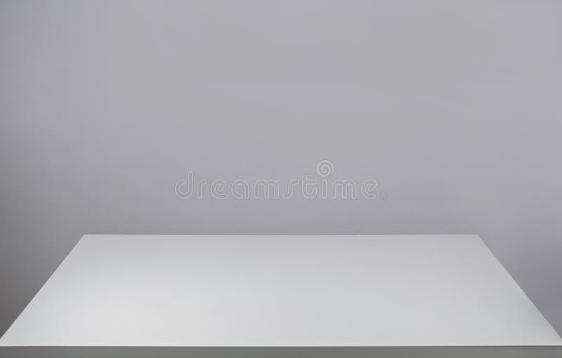 Lege witte bureaulijst en een lege grijze muur voor exemplaarruimte Grafisch middel voor ontwerp Vooraanzicht minimaliserende wer stock afbeelding