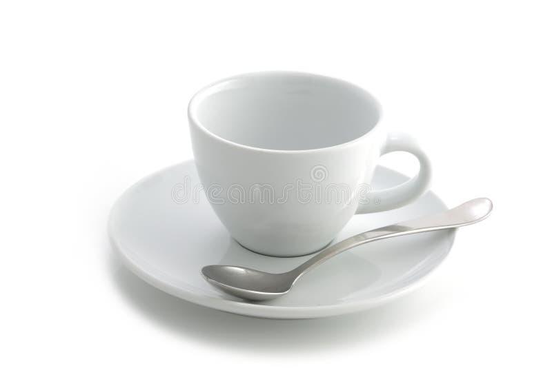 Lege witte die koffiekop en schotel en lepel op een witte achtergrond wordt geïsoleerd stock afbeeldingen