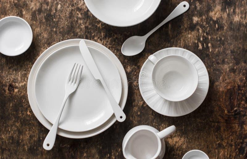 Lege witte dishware diende houten lijst, hoogste mening royalty-vrije stock afbeeldingen