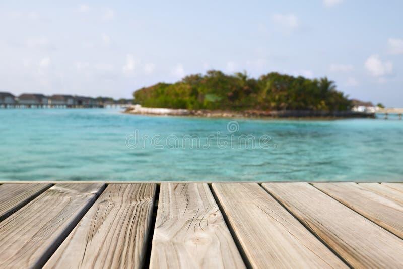Lege witte houten oppervlakte over onduidelijk beeld blauwe oceaanlagune en hemel en tropisch voor productplaatsing en vertoning royalty-vrije stock afbeelding