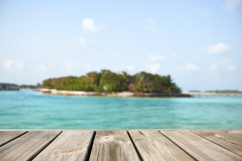 Lege witte houten oppervlakte over onduidelijk beeld blauwe oceaanlagune en hemel en tropisch voor productplaatsing en vertoning royalty-vrije stock foto