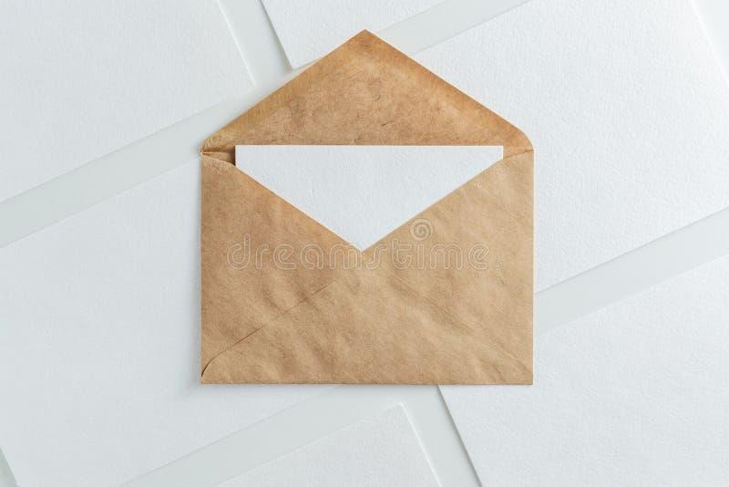Lege witte kaart in de envelop en het document van kraftpapier de bruine spot van het bladenmalplaatje omhoog stock foto