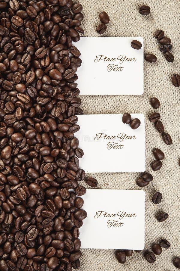 Lege witte kaart drie op textiel en koffiebonenachtergrond royalty-vrije stock fotografie