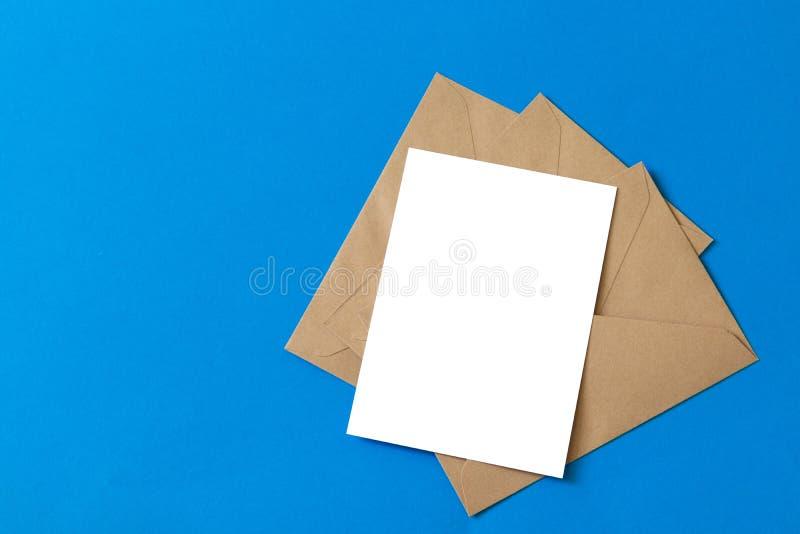 Lege witte kaart met van de het pakpapierenvelop van kraftpapier het malplaatje omhoog spot stock fotografie
