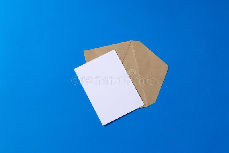Lege witte kaart met van de het pakpapierenvelop van kraftpapier het malplaatje omhoog spot stock afbeelding