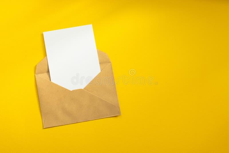Lege witte kaart met van de het pakpapierenvelop van kraftpapier het malplaatje omhoog spot stock foto