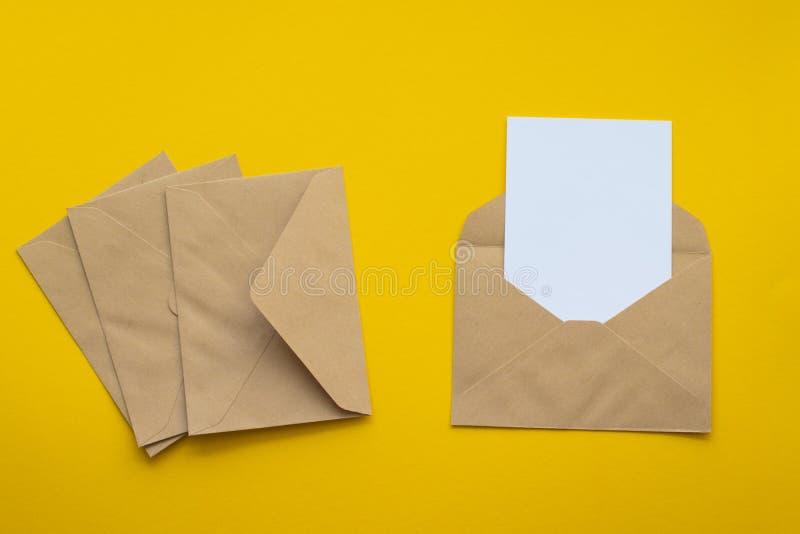 Lege witte kaart met van de het pakpapierenvelop van kraftpapier het malplaatje omhoog spot royalty-vrije stock afbeeldingen