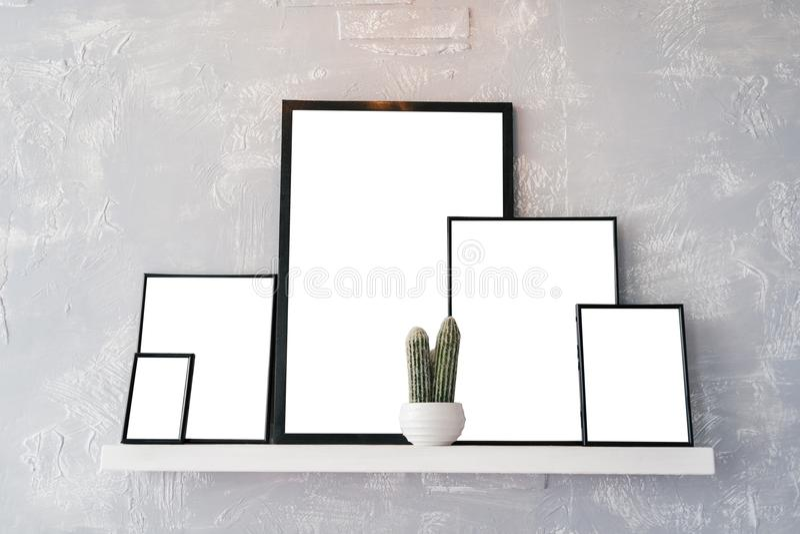 Lege lege witte kaarten met ruimte voor tekst in houten fotokaders Witte pot met cactus en fotokaders op witte plank stock foto