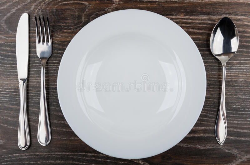 Lege witte plaat, mes, vork en lepel op lijst royalty-vrije stock afbeelding