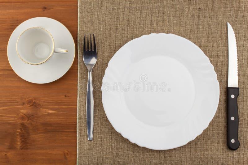 Lege witte plaat met mes en vork op een houten lijst Het wachten op Voedsel Huis het dineren Direct boven mening van lijst het pl royalty-vrije stock afbeelding