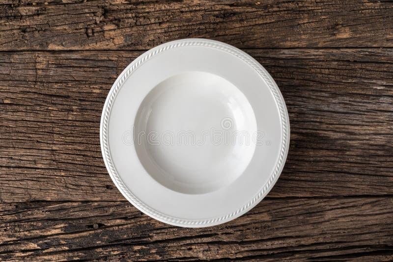 Lege witte plaat op houten lijst stock afbeeldingen
