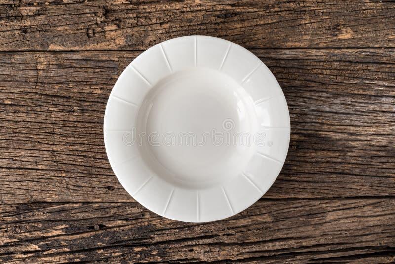 Lege witte plaat op houten lijst stock foto