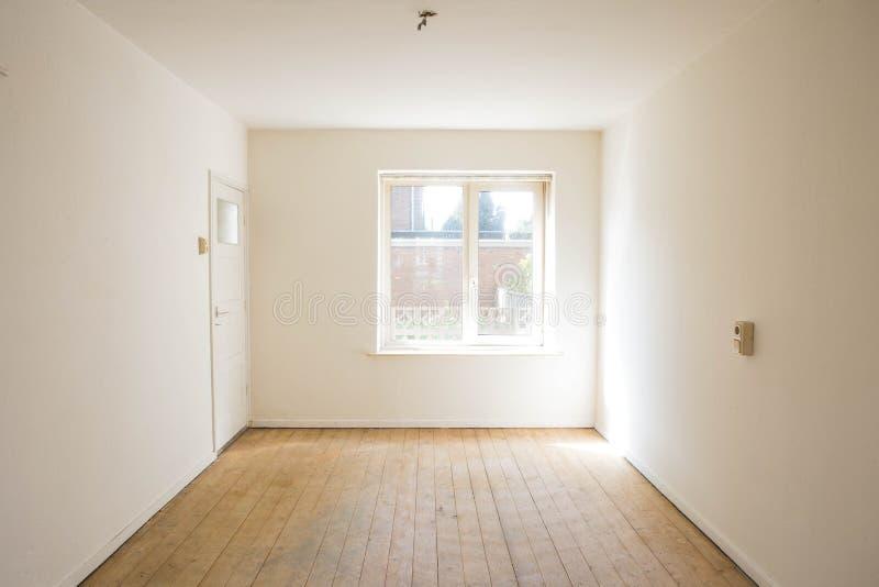 Lege witte ruimte met houten parketvloer vóór vernieuwing stock afbeelding