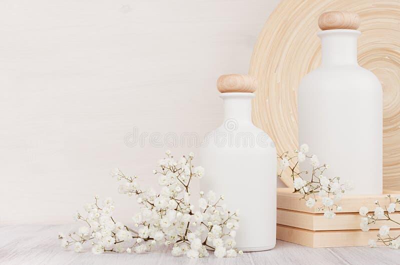 Lege witte schoonheidsmiddelenflessen met kleine bloemen op witte houten raad, exemplaarruimte Binnenlands stock afbeelding