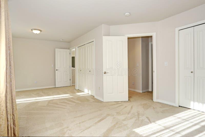 Lege zon gevulde ruimte met van de tapijtvloer en room muren stock foto's