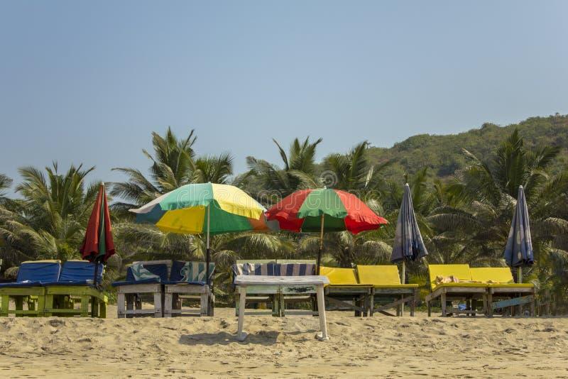 Lege zonlanterfanters onder de multi-colored strandparaplu's op het gele zand tegen de groene palmen onder een duidelijke blauwe  stock afbeeldingen