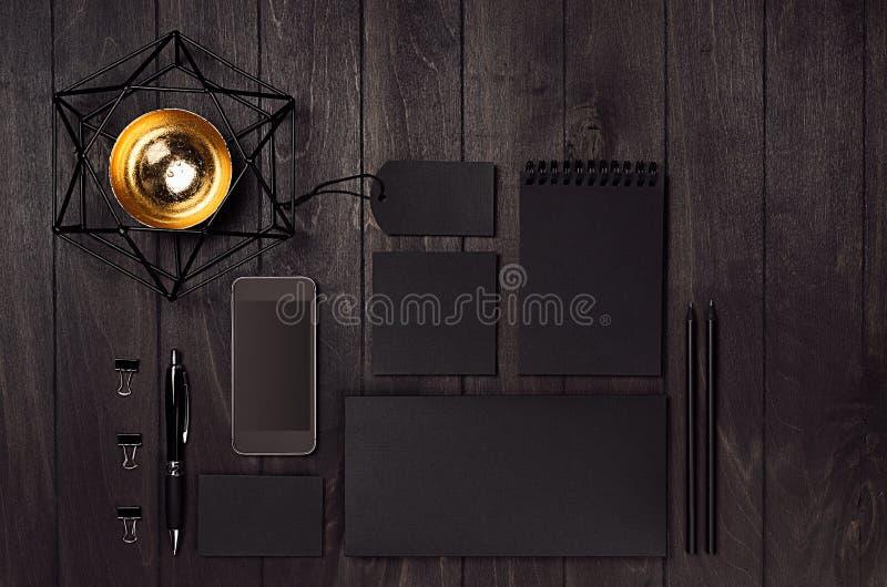 Lege zwarte bedrijfsdiekantoorbehoeften met telefoon, koffiekop, gouden decoratie op donkere elegante houten lijst wordt geplaats royalty-vrije stock foto's