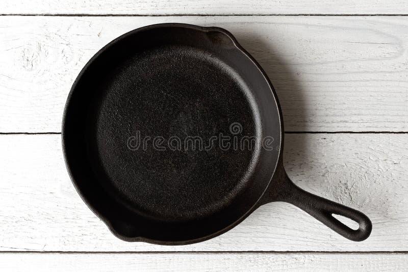 Lege zwarte die gietijzerpan op wit geschilderd hout van ab wordt geïsoleerd royalty-vrije stock afbeelding