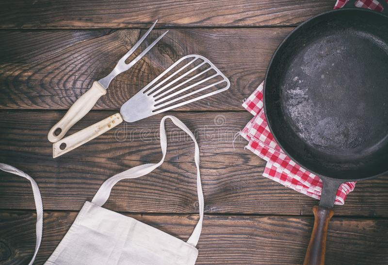 Lege zwarte gietijzerpan en kokende werktuigen royalty-vrije stock foto