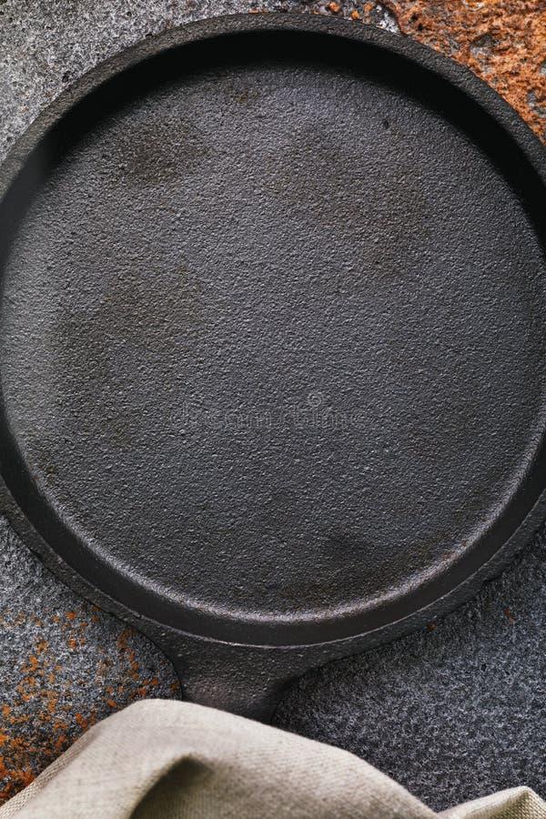 Lege zwarte gietijzerpan op een oude protvine met exemplaarruimte stock foto