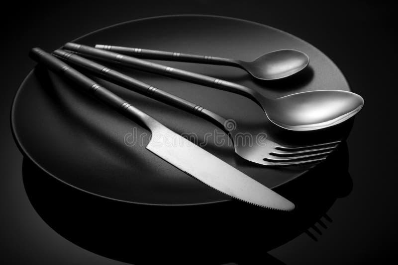 Lege zwarte plaat met mes en vork, lepel op een zwarte royalty-vrije stock fotografie