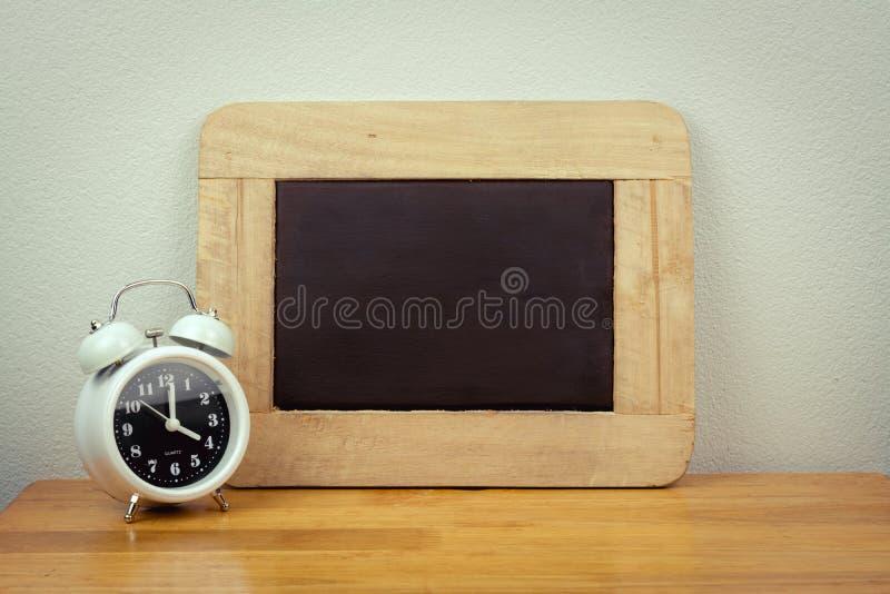 Lege zwarte raad en klok stock foto