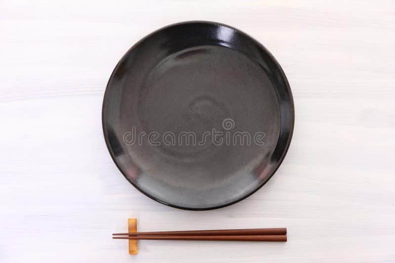 Lege zwarte schotel op de witte houten lijst met eetstokjes stock foto's