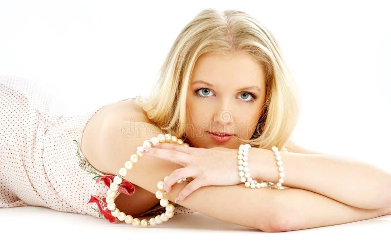 Legen blond im rosafarbenen Kleid mit Perlen lizenzfreie stockbilder