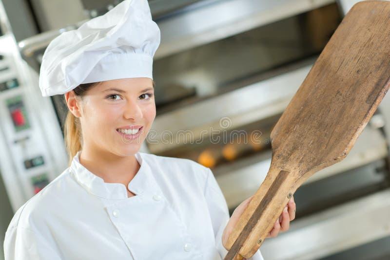 Legen des Brotes in Ofen lizenzfreie stockbilder