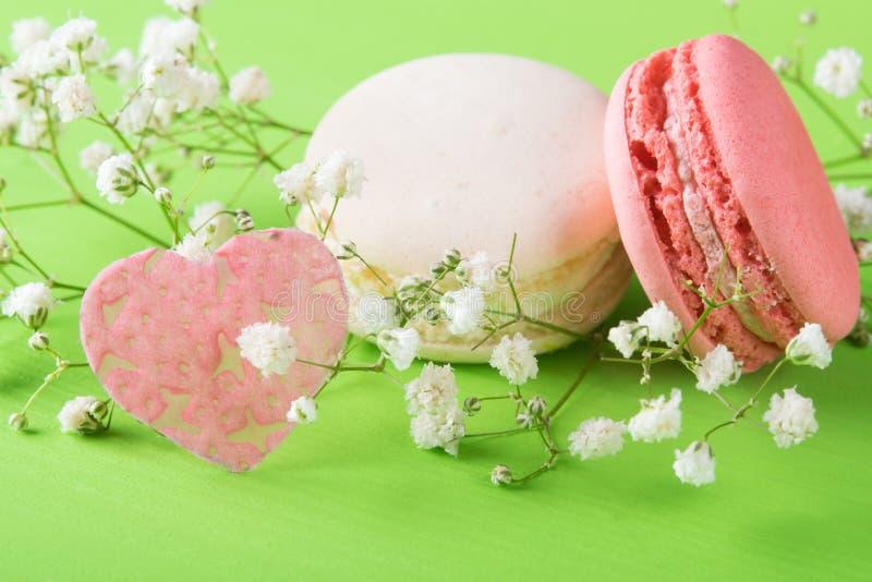 Legen empfindliches Makkaroni zwei mit einer weißen Blume und ein Herz auf einen hellgrünen Hintergrund stockbild