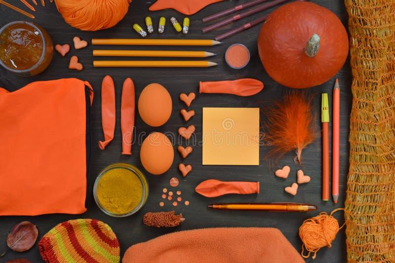 Legen Sie flach mit den orange Gegenständen, die zusammen auf Braun gemischt werden stockfotografie
