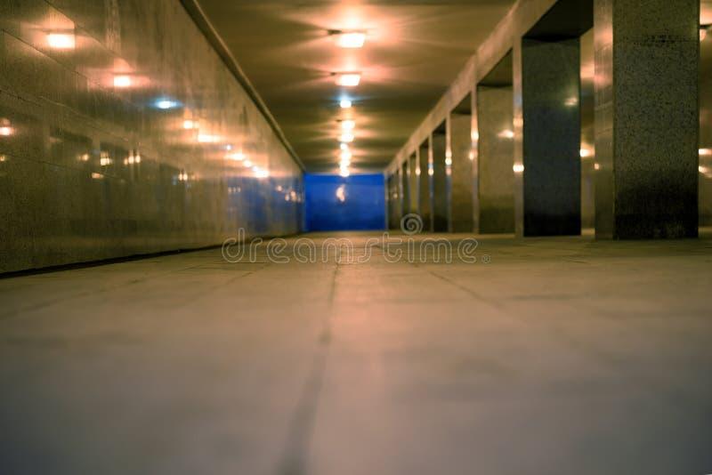 Legen Sie untertägigen Fußgängerübergang an der Dämmerung mit brennenden Lichtern vom niedrigeren Winkel einen Tunnel an stockbilder