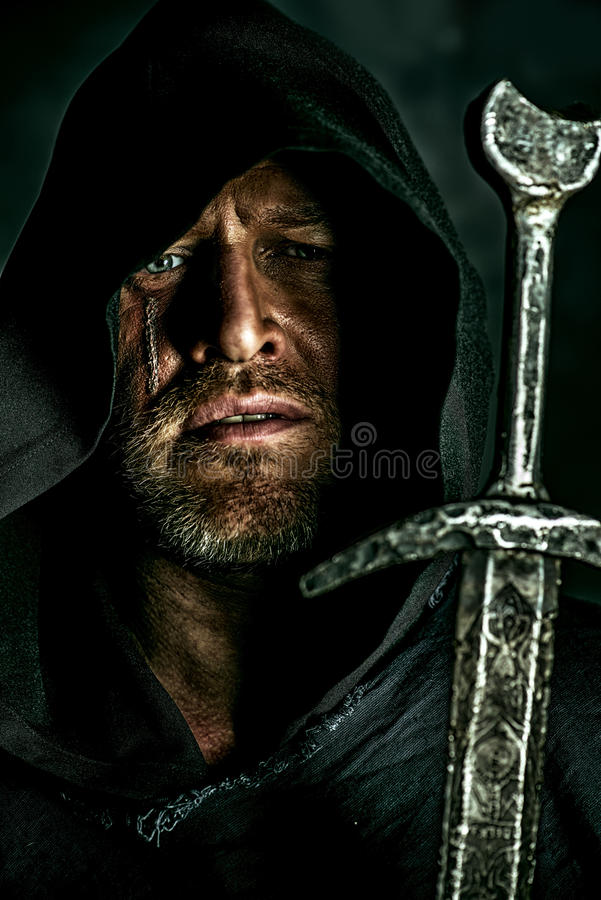 Legend. Portrait of a courageous warrior wanderer in a black cloak and sword in hand. Historical fantasy royalty free stock photography