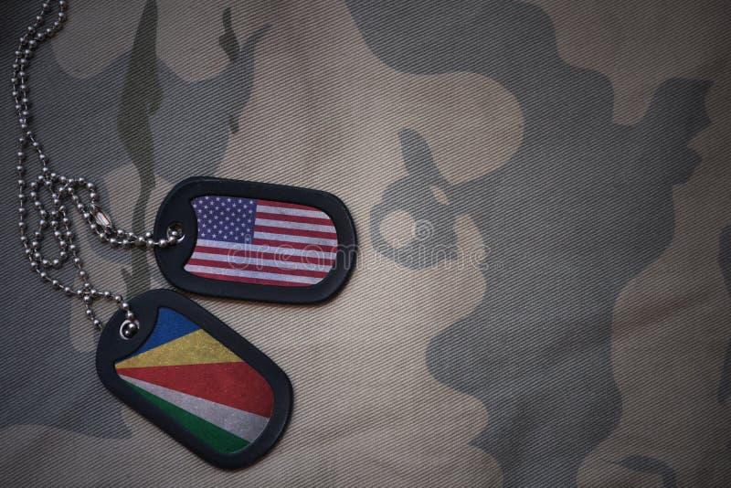 legerspatie, hondmarkering met vlag van de Verenigde Staten van Amerika en Seychellen op de kaki textuurachtergrond stock foto