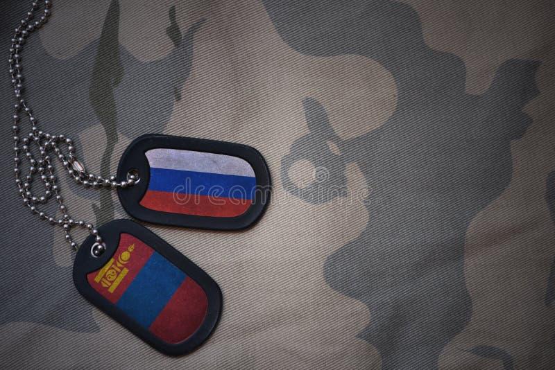 legerspatie, hondmarkering met vlag van Rusland en Mongolië op de kaki textuurachtergrond stock afbeeldingen